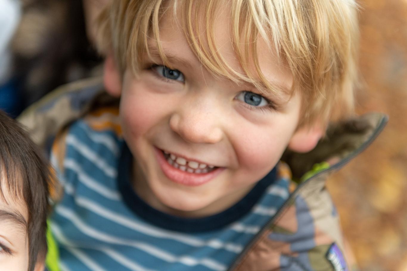 Un enfant de la maternelle qui nous sourit